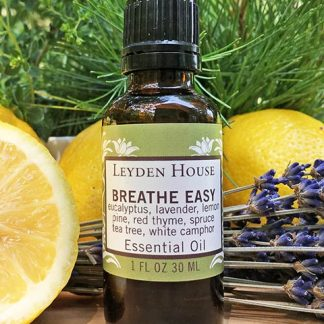 A photo of Breathe Easy essential oil blend in an amber bottle surrounded by lemons, lavender and greenery.